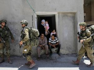 Israeli troops search a Palestinian home in the West Bank