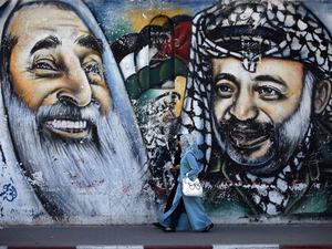 Palestinian women walk past a mural depicting late Hamas spiritual leader Sheikh Ahmed Yassin (L) and late Palestinian leader Yasser Arafat.
