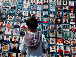 A Palestinian boy looks at pictures of Palestinian political prisoners being held by Israel.